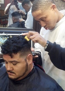 Federico barbering student showing how he finishes the back of a client's head