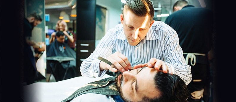 Federico Barbering student giving a client a close shave with a straight razor