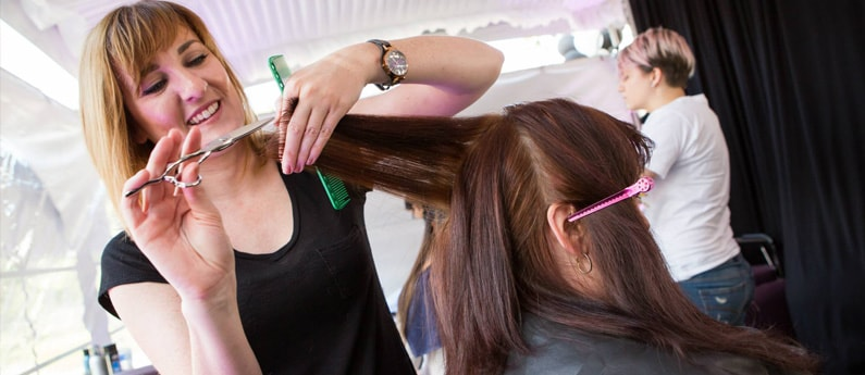 A student in the Federico Cosmetology Program cutting a client's hair
