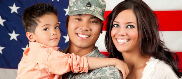 A veteran and his family in front of an American flag