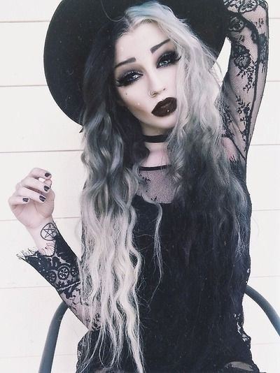 A trendy Goth look with dark lips, black and white long hair, lace top and a big, black hat.
