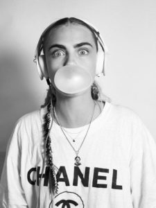 Model showing off great eyebrows while wearing a headset and blowing a chewing gum bubble