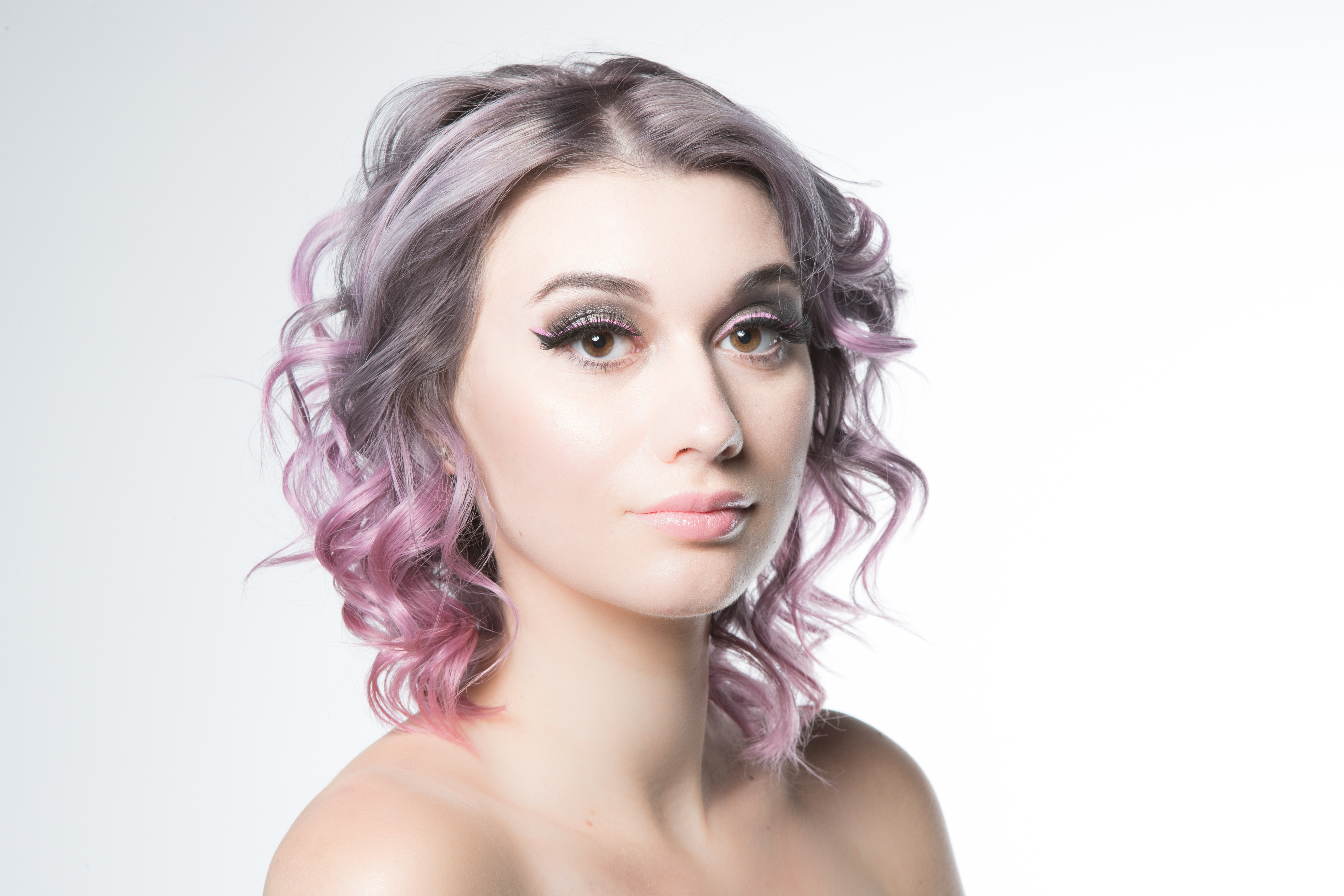 Model with shoulder-length wavy silver-lilac hair fading into pink at the ends.