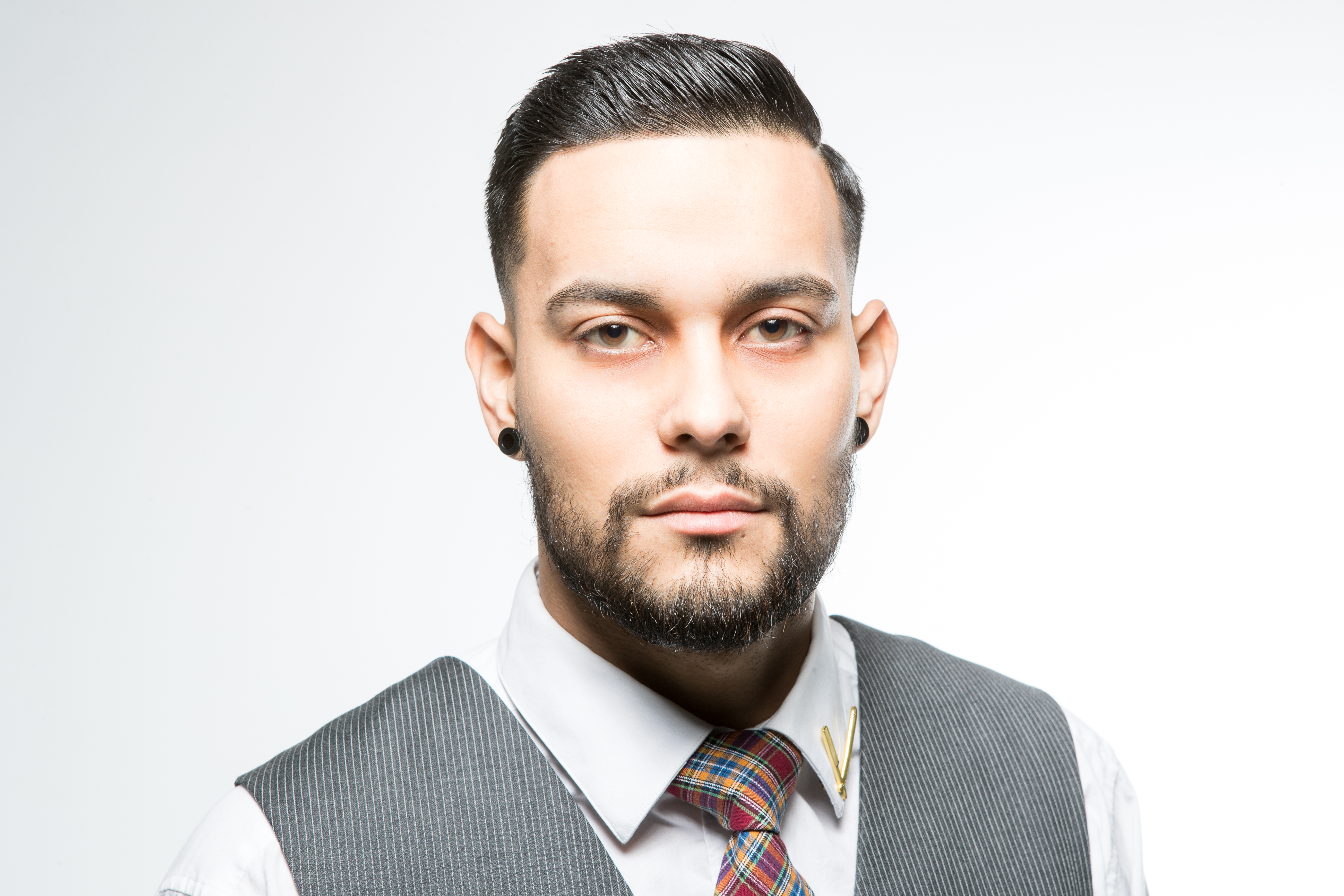 Model wearing a shirt and tie and showing a modern short style and groomed short beard.