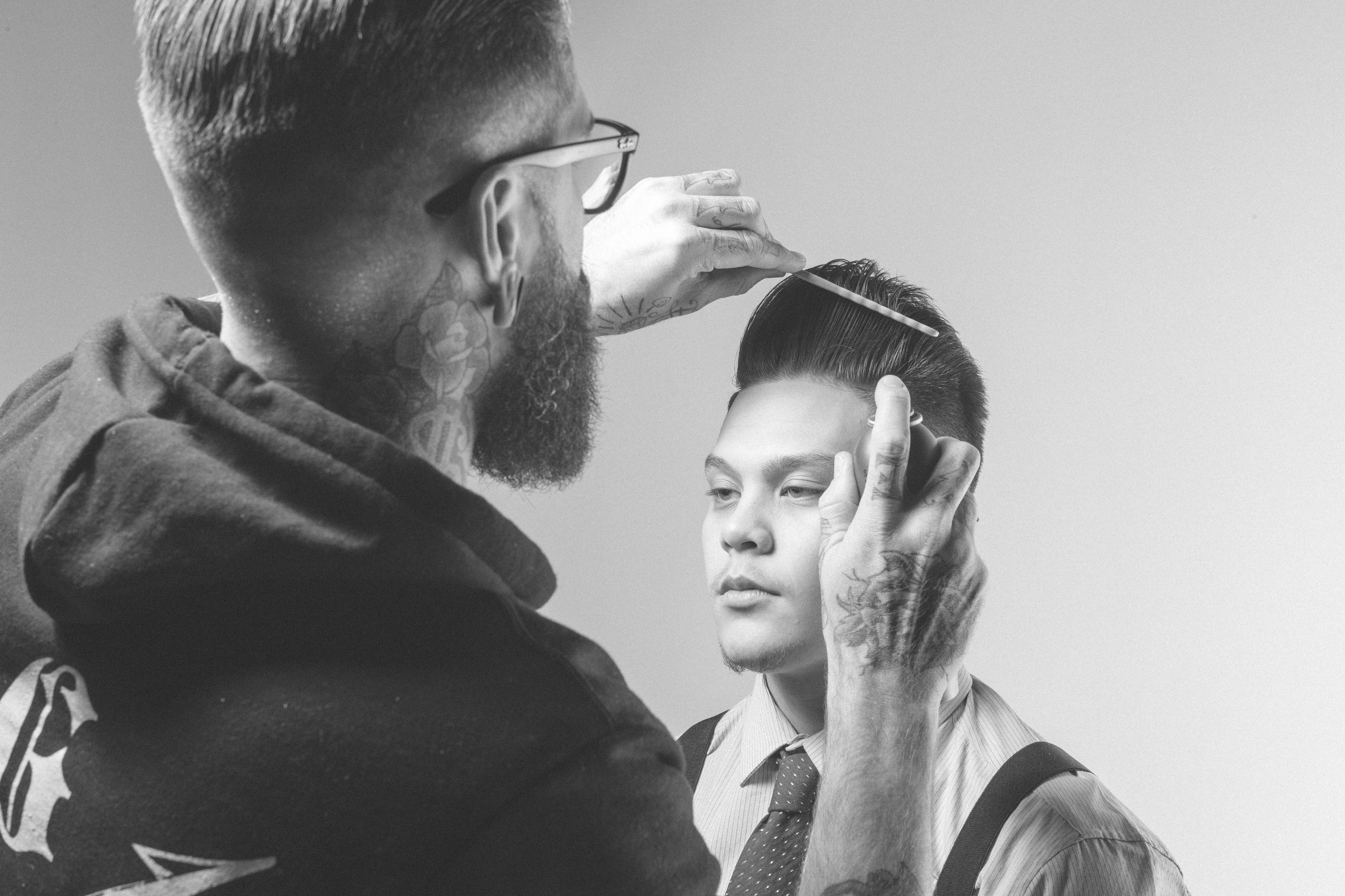 Model wearing a shirt and tie and showing a modern pompadour style getting prepped for the shoot