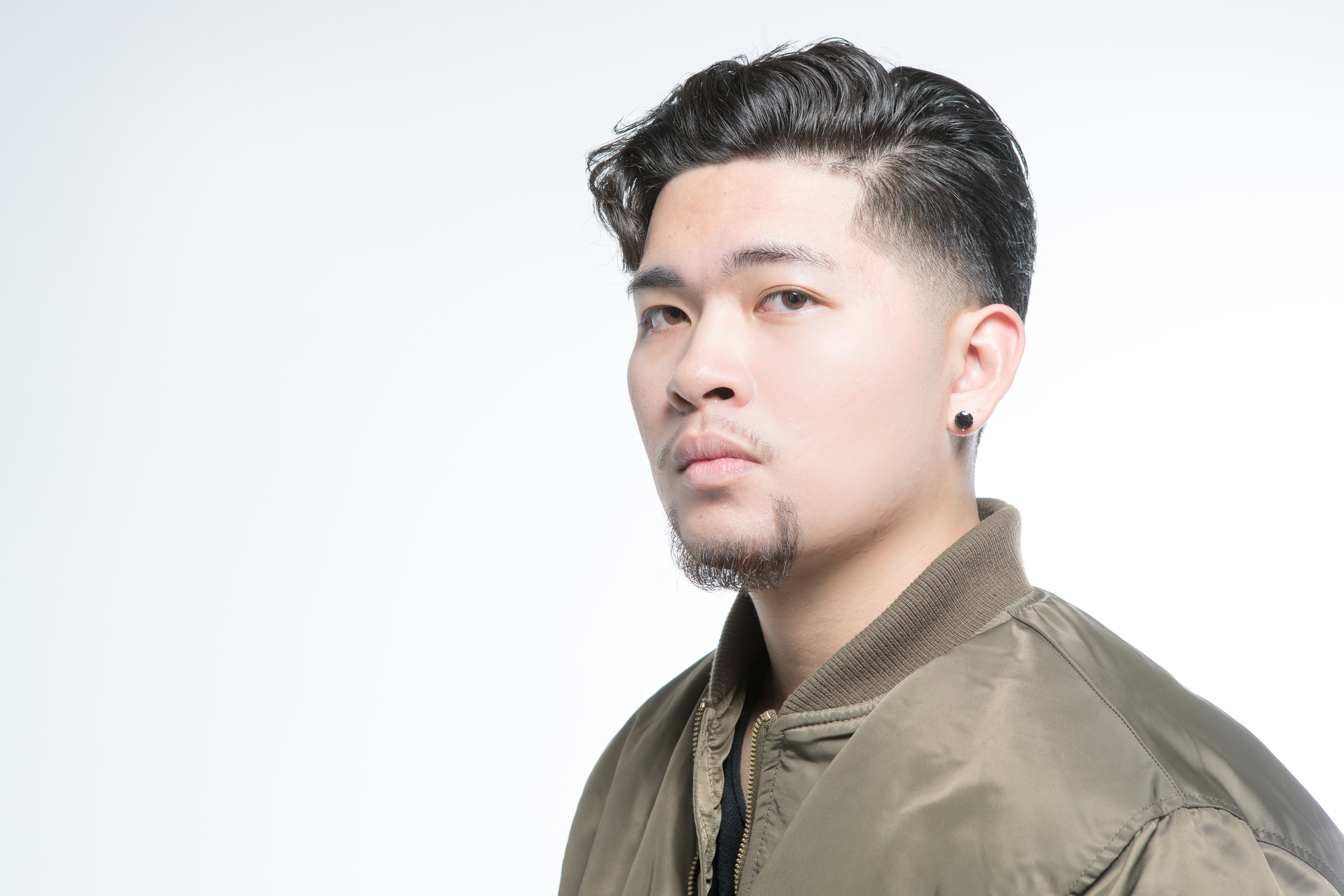 Model wearing a bomber jacket showing a short haircut and groomed goatee