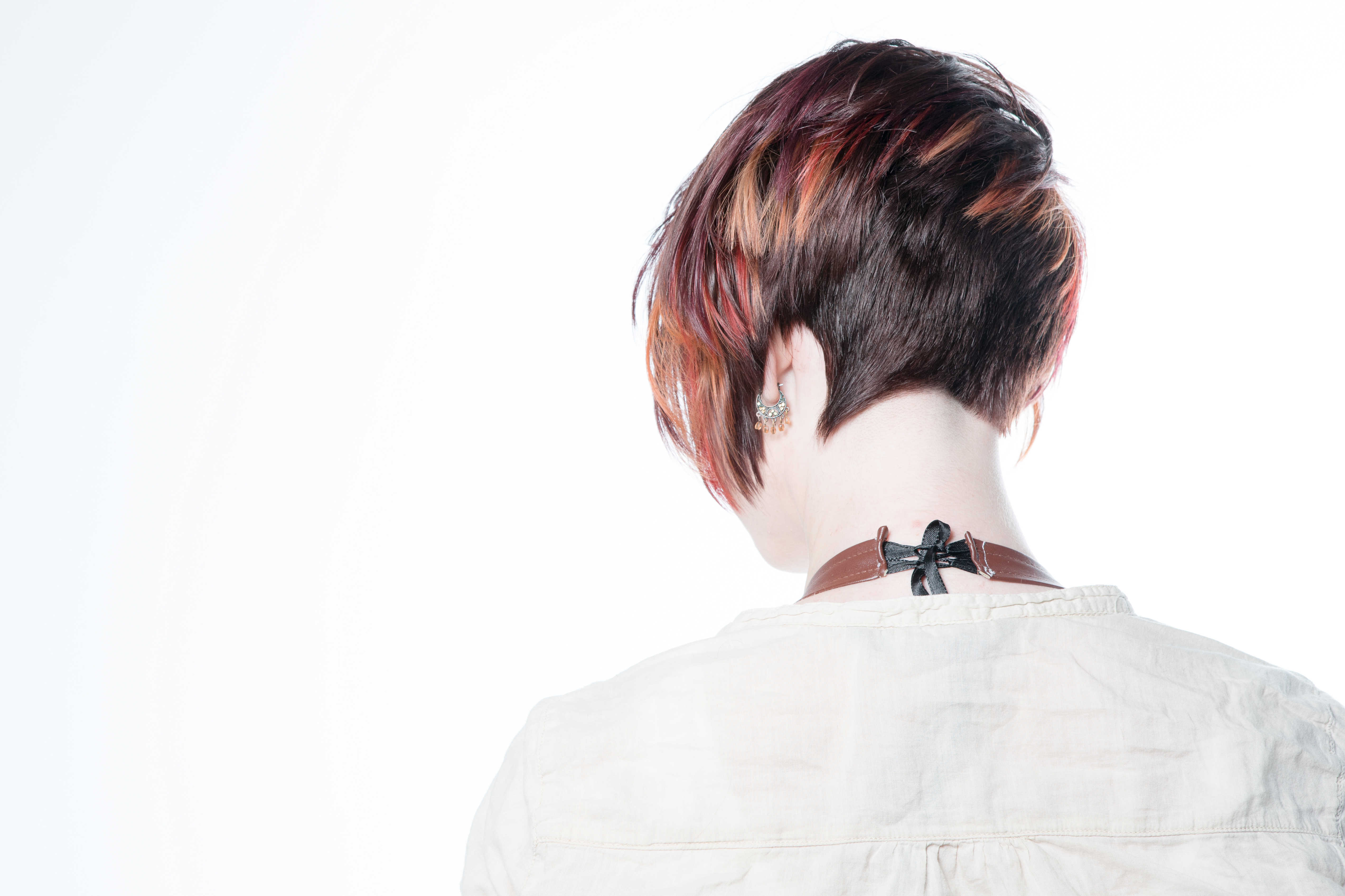 Model with a pixie cut that has orange highlights at the ends, view from the back