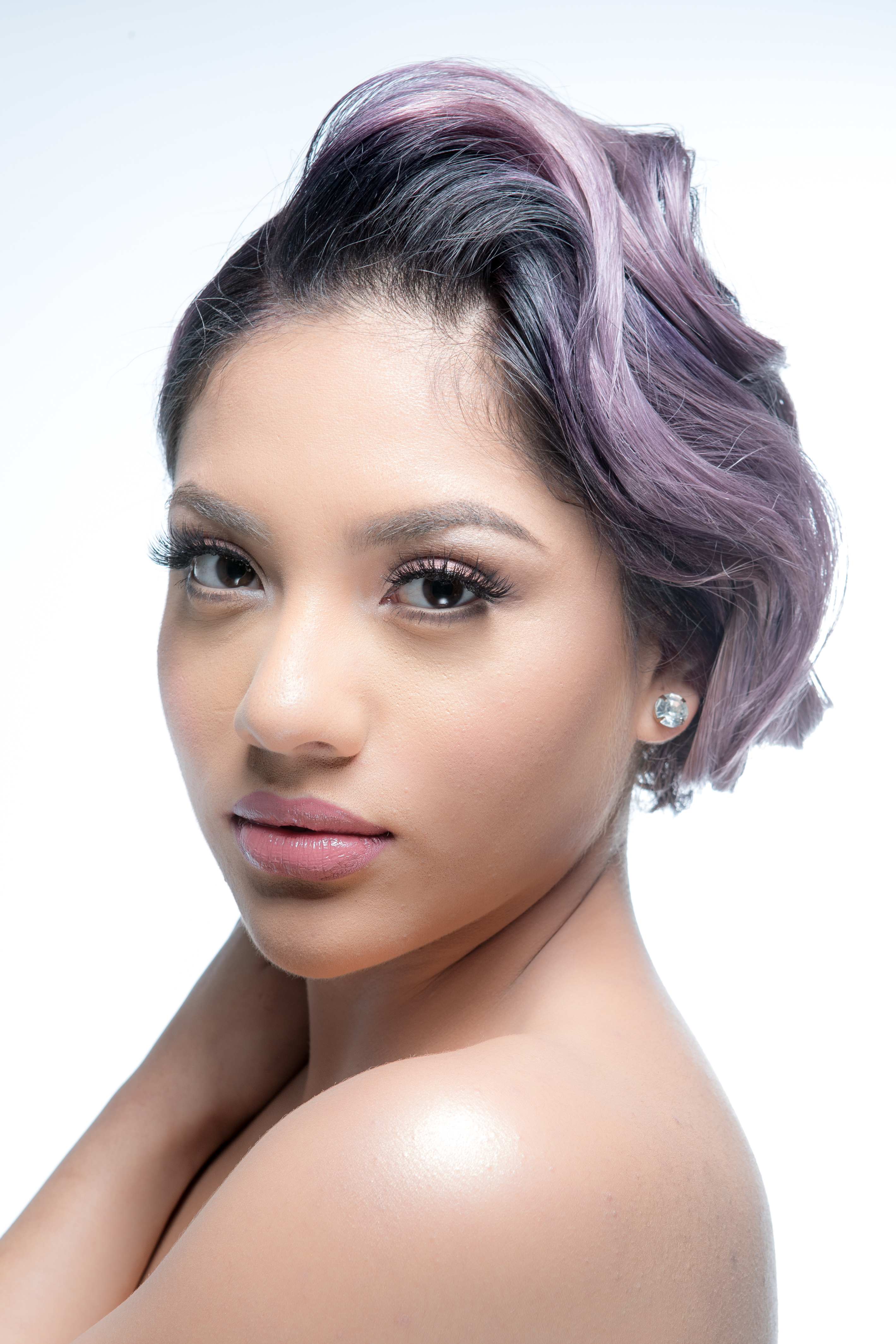 Model with pastel-lilac hair that is swept up in a wavy updo