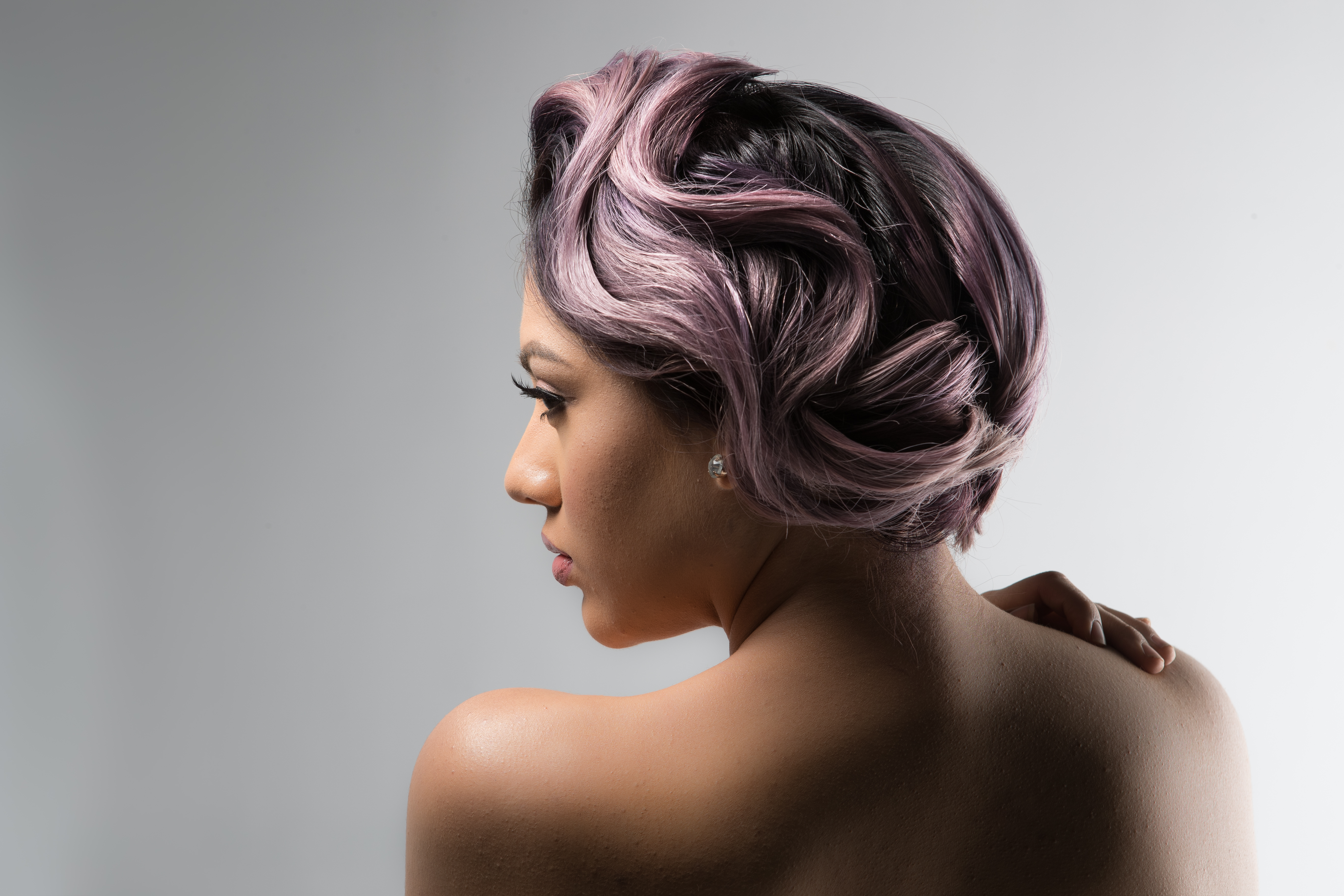 Model with pastel-lilac hair that is swept up in a wavy updo from another angle