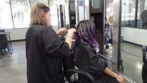Student working on a model's long black, pink and purple hair before a photoshoot.