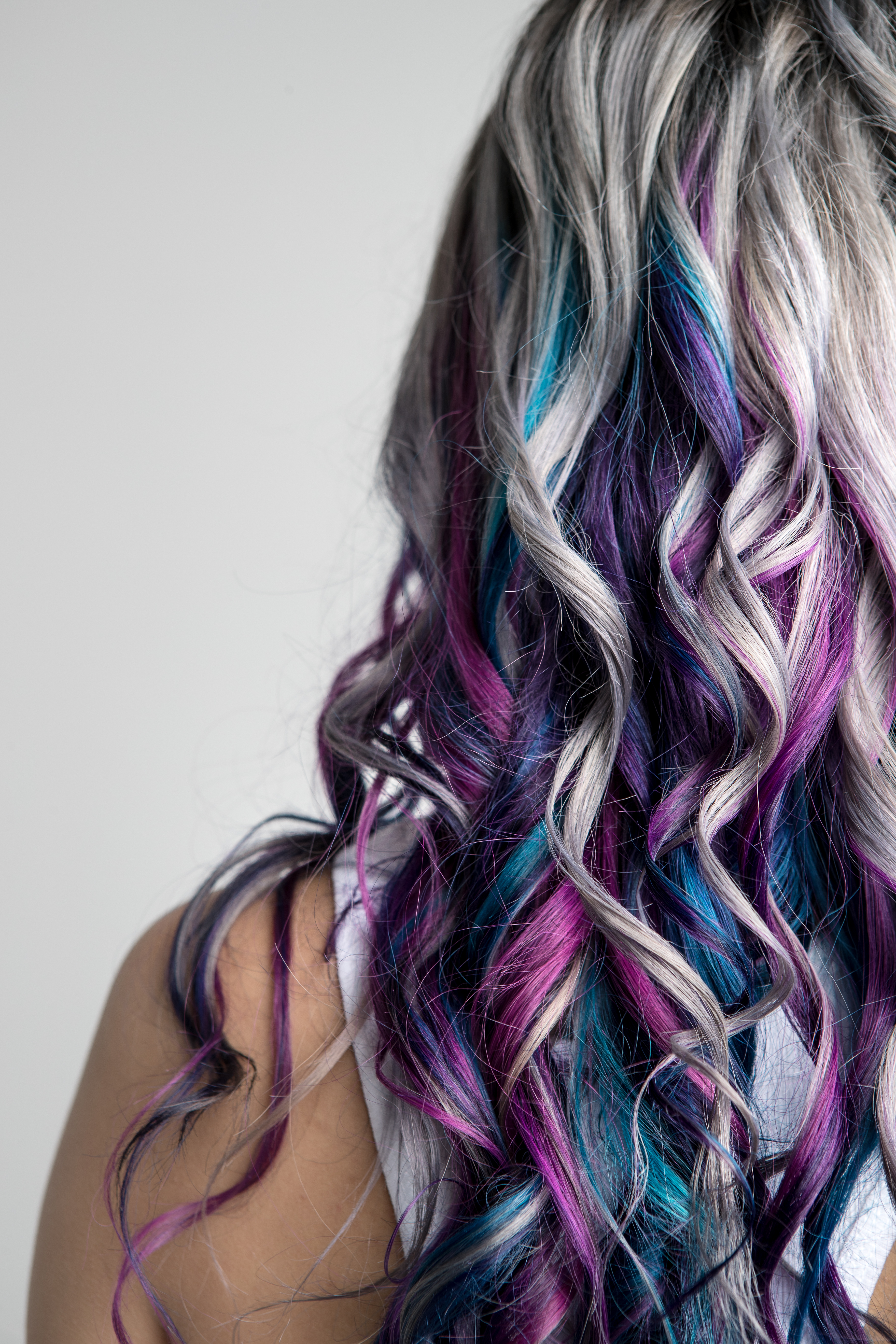 Back view of a long hair style. Hair is mostly silver with blue and purple streaks mixed at the ends.