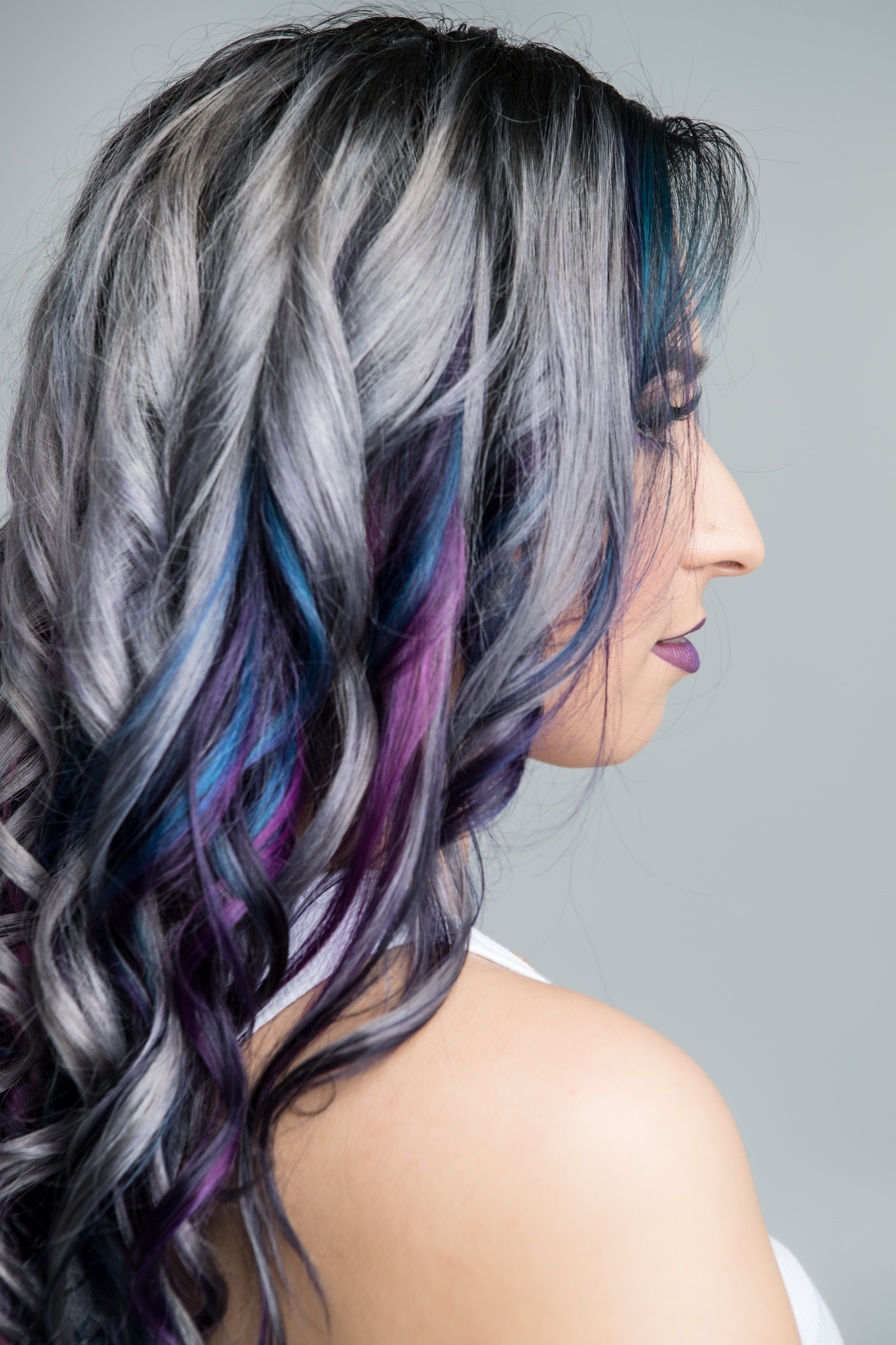 Side view of a long hair style. Hair is mostly silver with blue and purple streaks mixed at the ends.