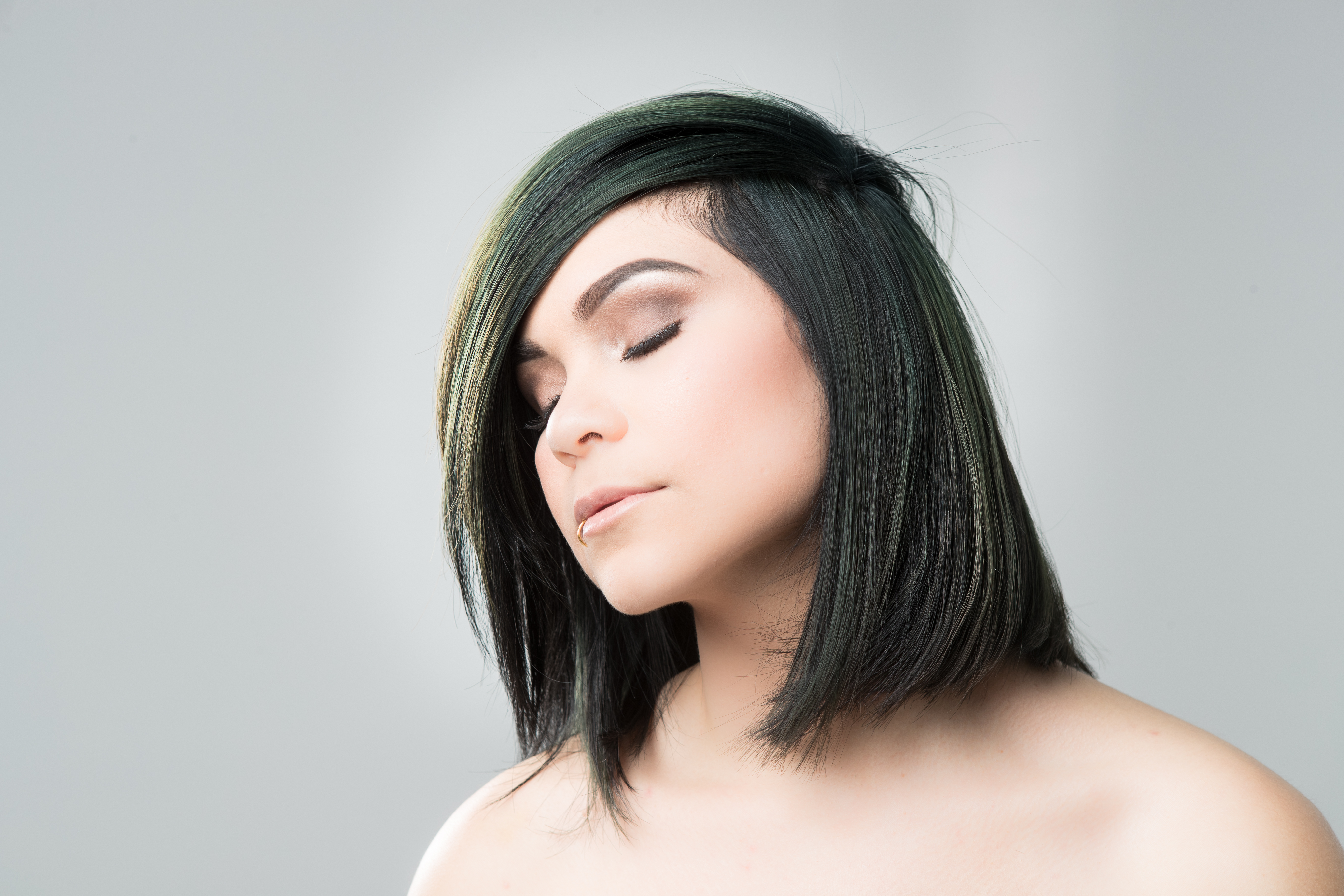 Model showing a shoulder-length bob with a dark forest-green color.