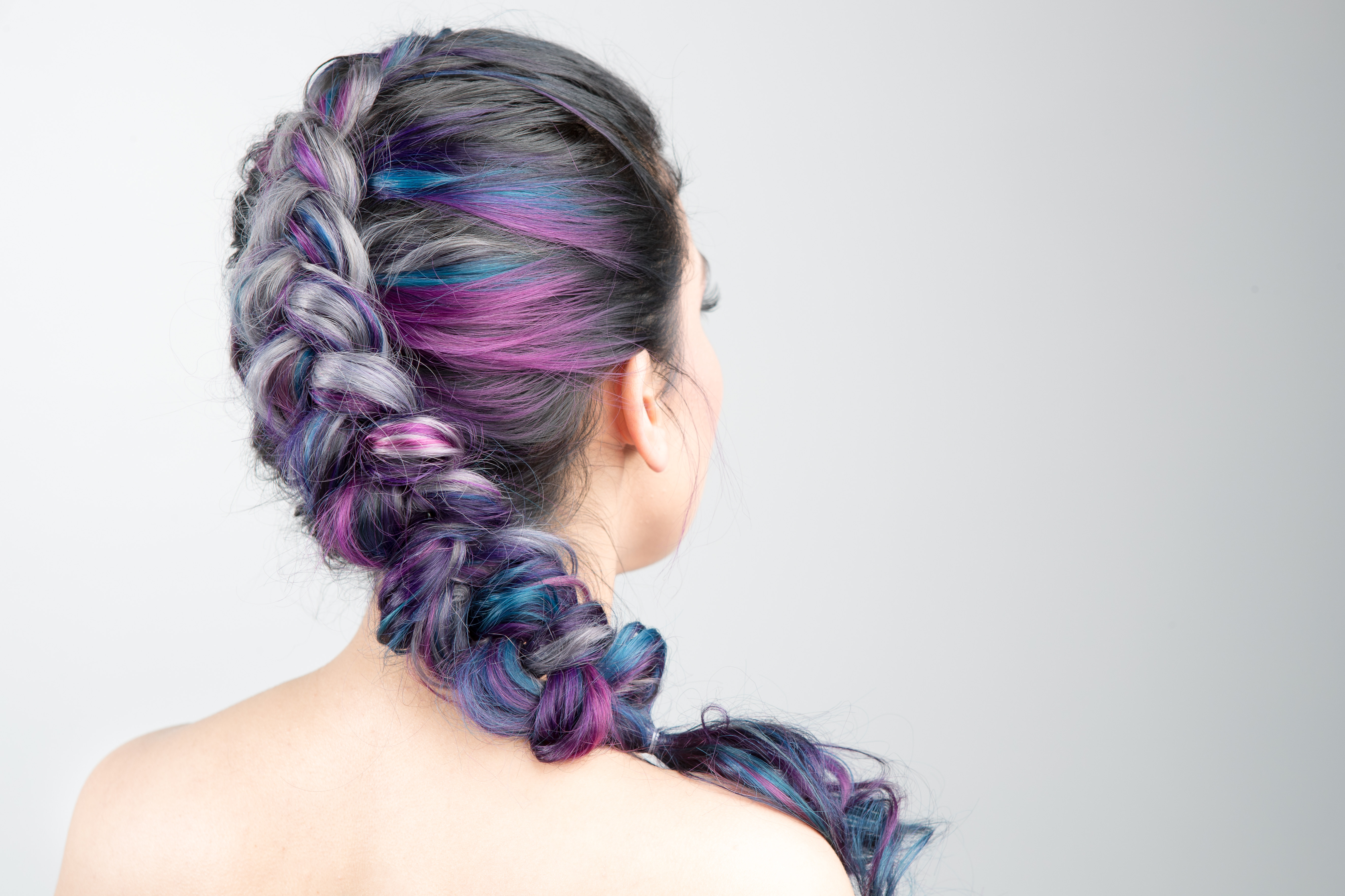 Back view of a long hair style swept up in a braid. Hair is mostly silver with blue and purple streaks mixed at the ends.