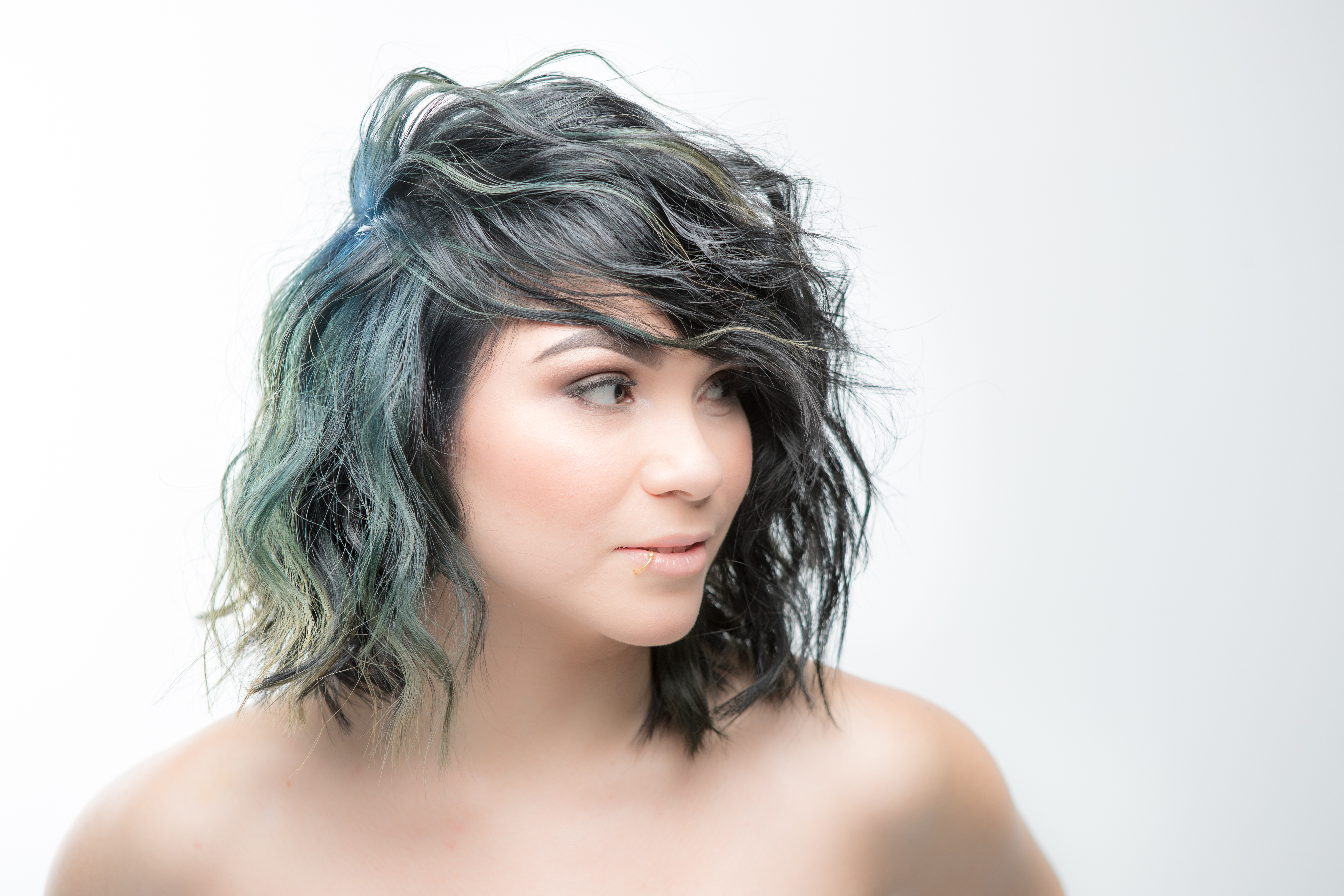 Shoulder-length tousled bob with a wash of green through it.