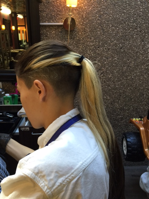 Bleached long hair pulled back, showing an undercut.