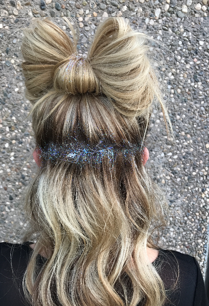 Cute updo with hair in the shape of a bow and covered in glitter.