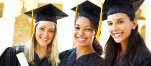Three young women celebrating their graduation with diplomas